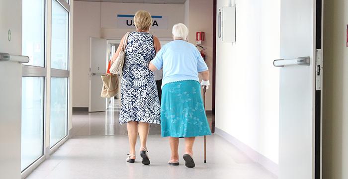 Moeder met dochter wandelt door gang verpleeghuis